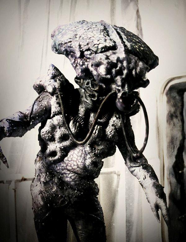 Groteske Kreatur, humanoid mit großem Kopf, Schläuchen am Mund und Zangenhänden.