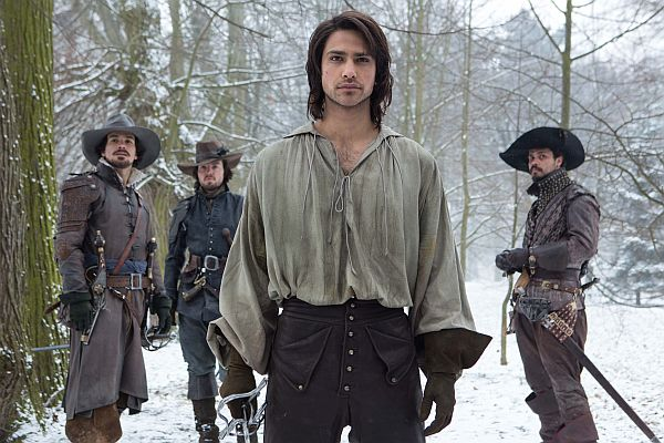 Drei Männer im verschneiten Wald. Alle tragen Degen und sehen entschlossen in die Kamera.