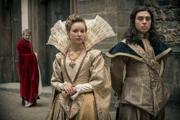 Ein Mann und eine Frau in prächtigen Gewändern des 17. Jahrhunderts, im Hintergrund ein Mann mit spitzen Bart und roter Robe.