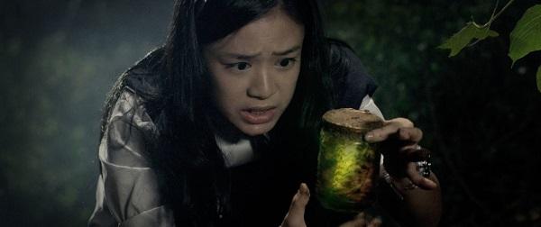 Ein junges Mädchen sieht angeekelt auf ein Glas mit einer grün leuchtenden Substanz.
