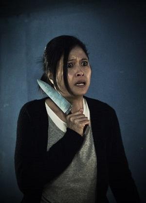 Eine asiatische Frau hält sich mit entsetzter Miene ein Messer an den Hals.