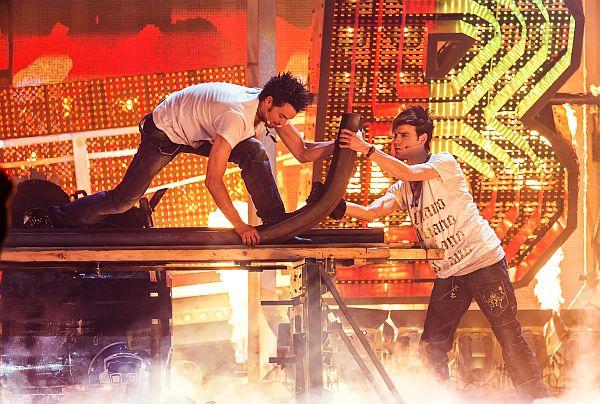 Zwei Männer auf einer Bühne. Gemeinsam biegen sie eine massive Eisenschiene hoch.