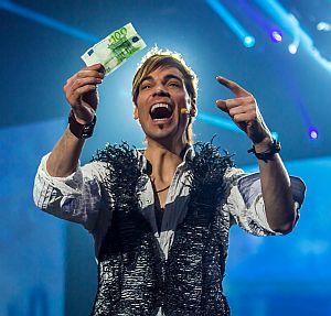 Ein Mann hält lachend einen 100-Euro-Schein hoch.