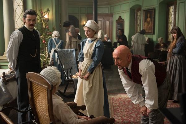 Ein Mann in Hemd und Weste beugt sich herab zu einer sitzenden Frau mit Haube. Neben beiden stehen ein weitere Mann in viktorianischer Kleidung und eine Frau in Schwesterntracht.