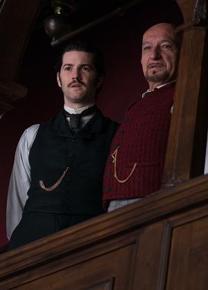 Zwei Männer in viktorianischer Kleidung schauen von einer Balustrade herab.