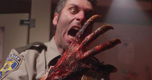 Ein Mann in Sheriff-Uniform blickt voller Entsetzen auf seine rechte Hand, die sich in eine blutige Klaue verwandelt.
