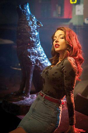 Eine Frau in eng anliegender Kleidung lehnt sich lasziv zurück. Im Hintergrund ist die Statue eines heulenden Wolfes zu sehen.