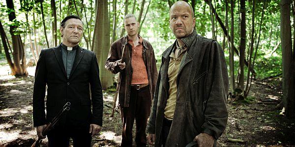 Drei Männer im Wald. Einer von ihnen ein katholischer Priester, sie haben ein Gewehr und einen angespitzten Pflock dabei.