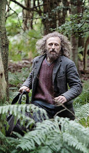 Ein bärtiger langhaariger Mann rennt gehetzt durch einen Wald zwischen Farnen entlang.