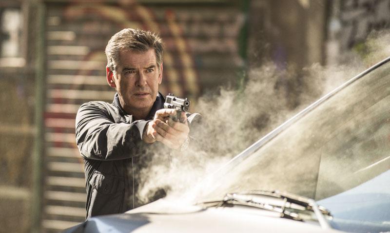 Ein Mann Anfang 60 steht mit erhobender Pistole hinter einem qualmenden Auto.