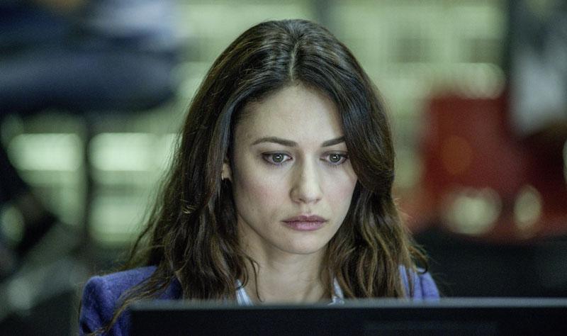 Eine Frau mit braunen offenen Haaren blickt konzentriert auf einen Computerbildschirm.