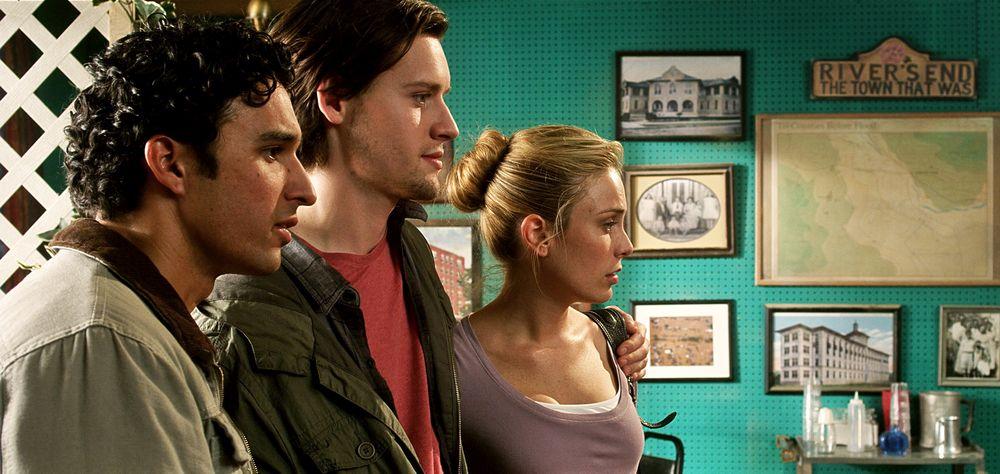 """Eine junge Frau und zwei junge Männer stehen nebeneinander. Sie schauen leicht verwundert nach rechts, doch was sie sehen wird nicht abgebildet. Im Hintergrund hängen Fotografien von alten Häusern, eine Landkarte und ein Schild """"River's End the town that was""""."""