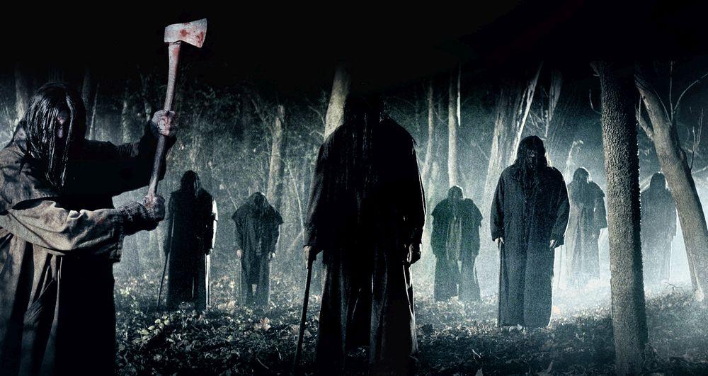 Neun dunkle Gestalten im dunklen, verregneten Wald. Ihre Gesichter sind von langen Haaren verdeckt. Sie tragen lange Mäntel und haben Äxte dabei.