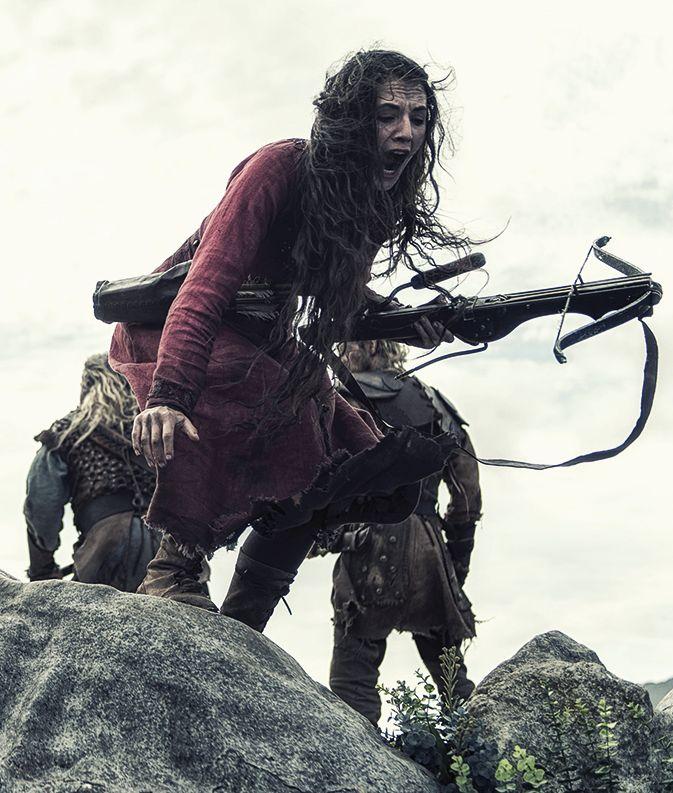 Eine Frau mit einer Armbrust steht schreiend am Rand einer Schlucht.