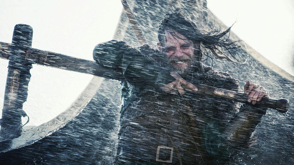 Ein bärtiger Wikinger hält im dichten Sturm die Ruderpinne mit zusammengebissenen Zähnen.