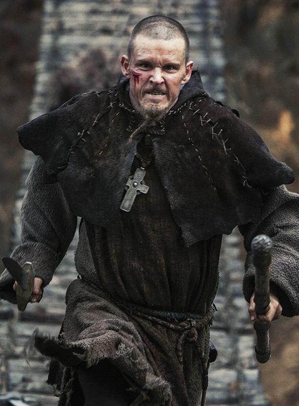 Ein Mann in Mönchskutte rennt mit verbissenem Gesichtsausdruck über eine Hängebrücke.