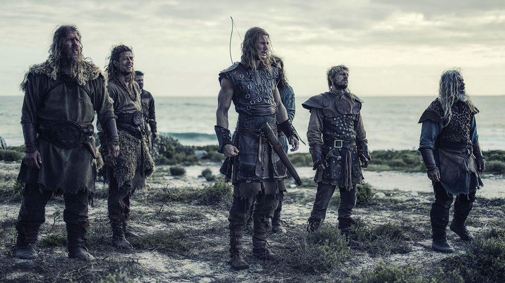 Sieben langhaarige und bärtige Männer in lederner Kluft stehen am Strand.