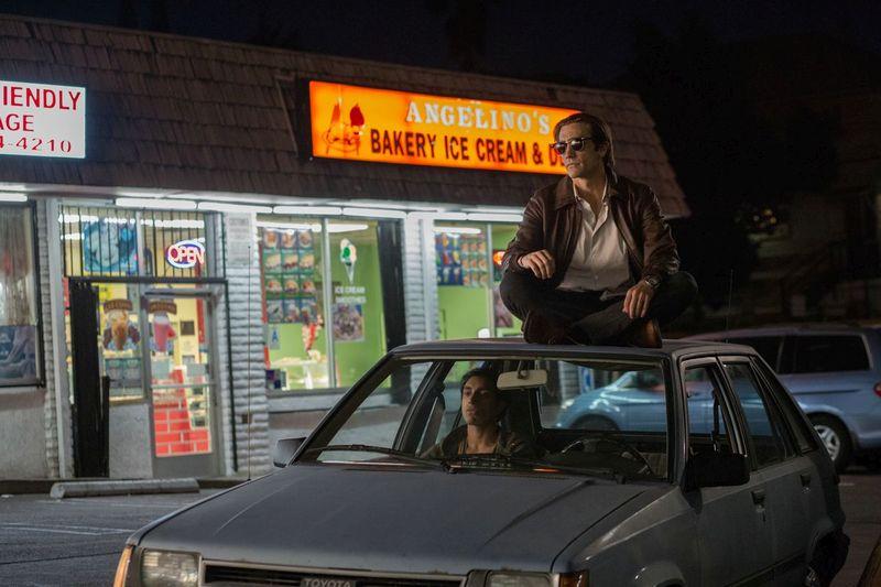 Nachtszene: Ein Auto steht vor einem hell erleuchteten Kiosk, auf dem Beifahrersitz sitzt ein Mann. Auf dem Autodach sitzt ein blasser Mann mit Sonnenbrille.