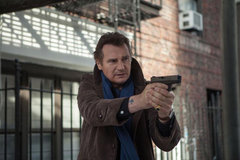 Szene aus Ruhet in Frieden: Liam Neeson hat in einem Hinterhof eine Pistole gezogen und richtet sie mit beiden Händen nach rechts.