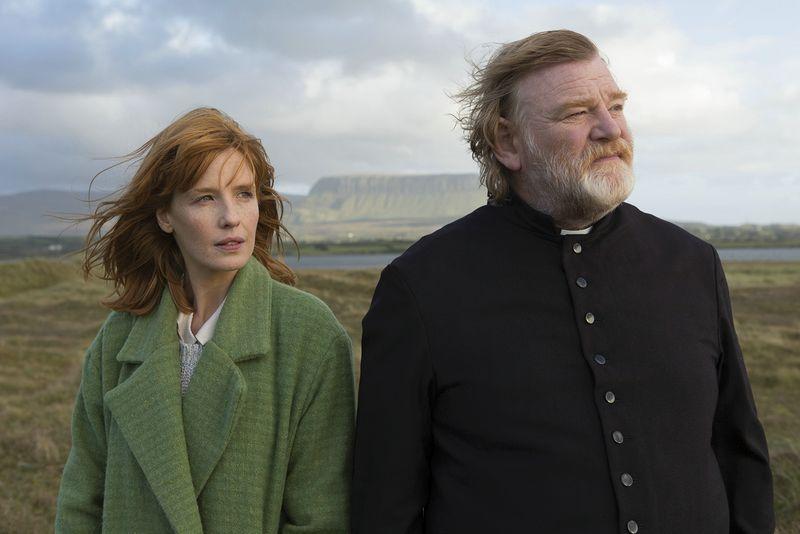 Eine junge Frau mit roten Haaren und ein älterer bärtiger Mann in Soutane in irischer Landschaft.