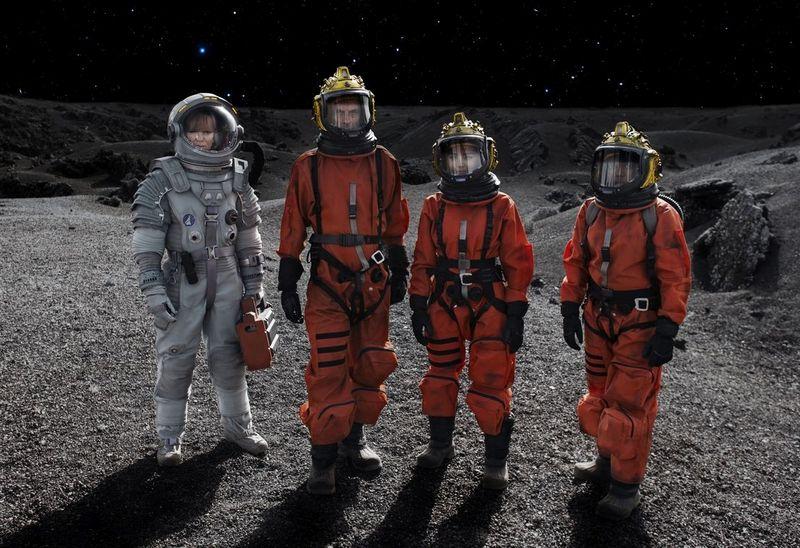 Vier Personen in Raumanzügen auf dem Mond.