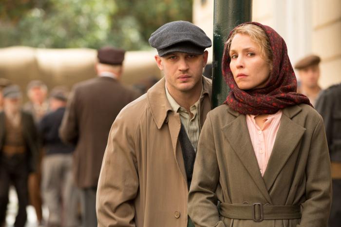 Ein Mann mit blau-grauer Mütze und eine blonde Frau mit rotem Kopftuch. Sie tragen einfache Kleidung im Stil der 50er, im Hintergrund ist eine größere Menschenmenge zu sehen.