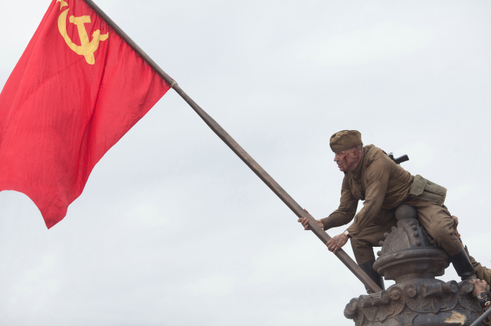 Ein Rotarmist hisst die Flagge der Sowjetunion.