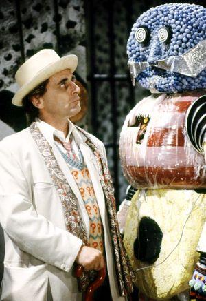 Ein Mann in hellem Anzug mit Hut, vor ihm steht ein Geschöpf aus riesigen Bonbons zusammengesetzt.