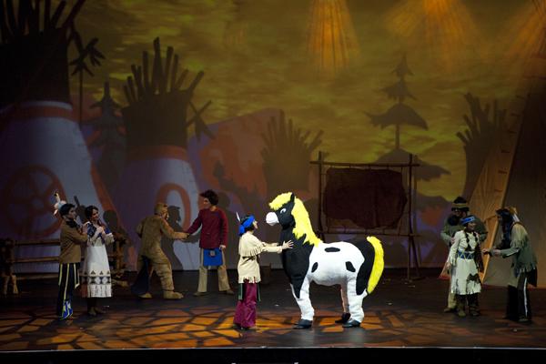 Eine Bühne mit Tipis und Menschen in Indianerkostümen. Im Zentrum ein kleiner Indianer und ein Pony.