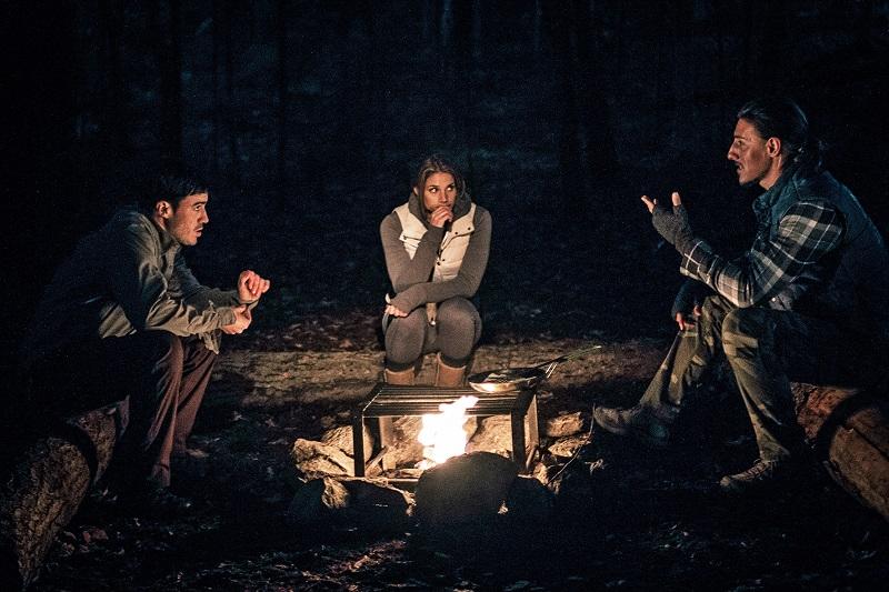 Eine Frau sitzt zwischen zwei Männern an einem Lagerfeuer nachts in der kanadischen Wildnis.