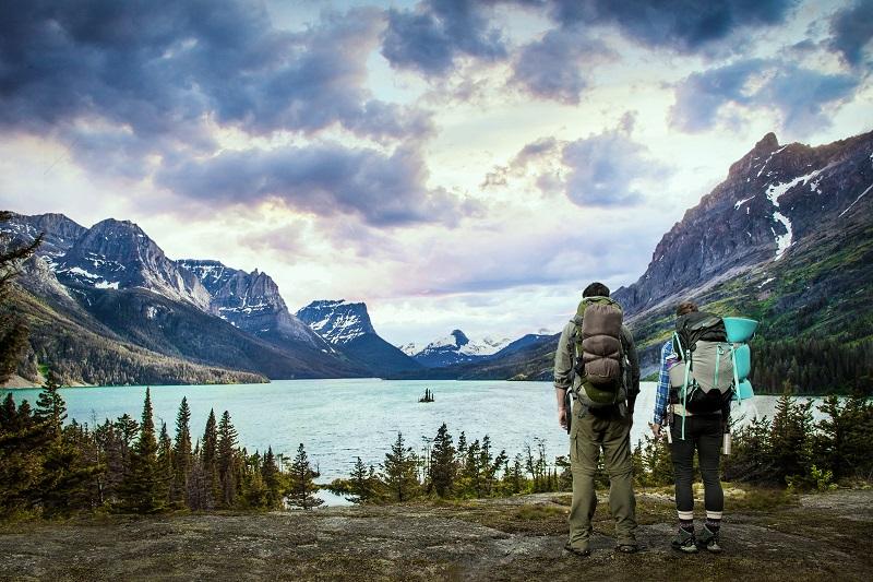 Ein See in den Bergen, davor ein Mann und eine Frau in Wanderkluft.