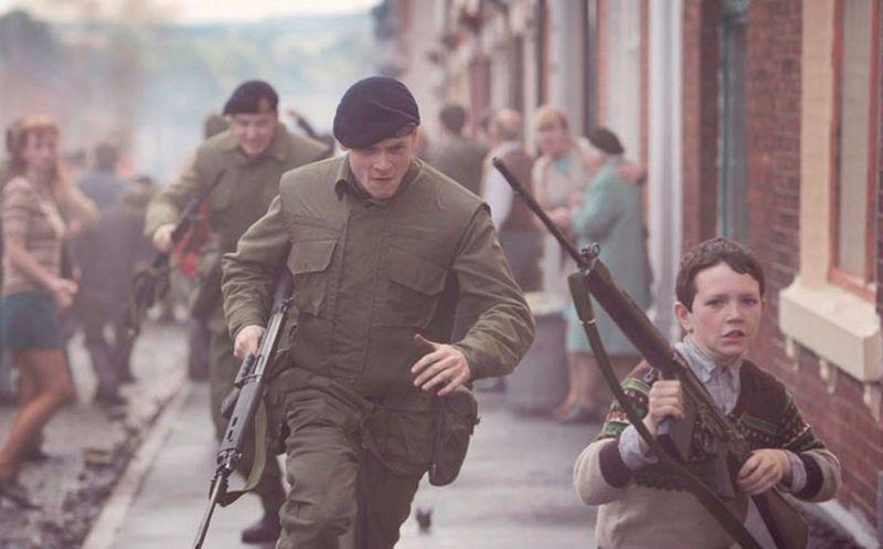 Zwei Männer in Uniformen verfolgen einen Jungen, der ein Gewehr in Händen hält durch eine Straße voller Menschen.