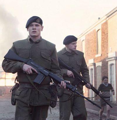 Zwei Männer in Uniformen mit Gewehren gehen durch eine Straße mit Backsteinhäusern. Im Hintergrund läuft ein Junge in kurzen Hosen.