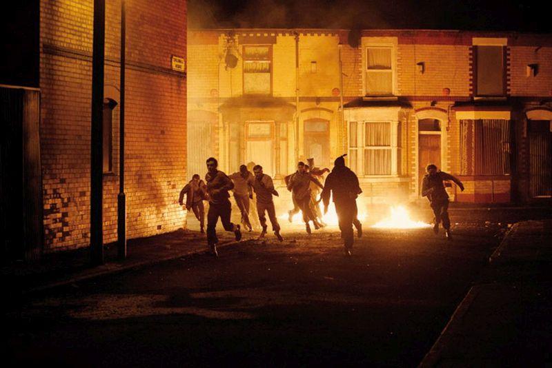 Eine Gruppe von jungen Männern rennt durch eine nächtliche Straße. Hinter ihnen brennt etwas am Boden, große Flammen beleuchten die Szene.