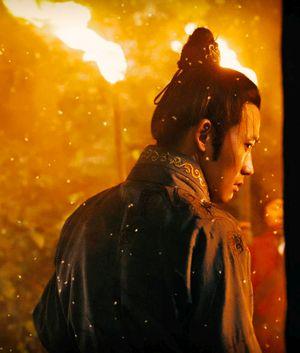Ein chinesischer Mann im Profil, es schneit, im Hintergrund brennen Fackeln.