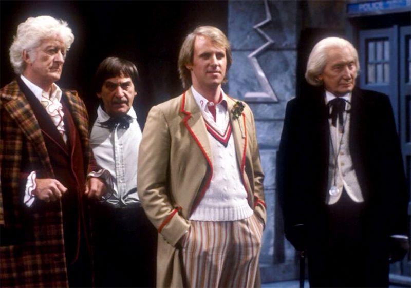 Vier Männer, drei davon im fortgeschrittenen Alter, in unterschiedlichsten Outfits in einer steinernen Halle. Im Hintergrund ist eine blaue Police Box zu sehen.