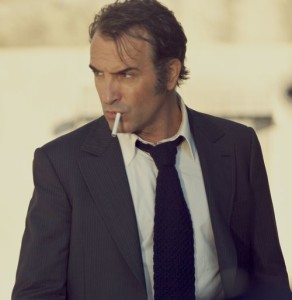 Ein Mann, um die 40, im Anzug. Er raucht eine Zigarette und schaut misstrauisch zur Seite.