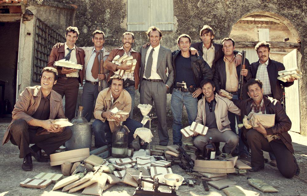 Szene aus La French: Eine Gruppe von Männern posiert mit beschlagnahmten Drogenutensilien und Waffen.