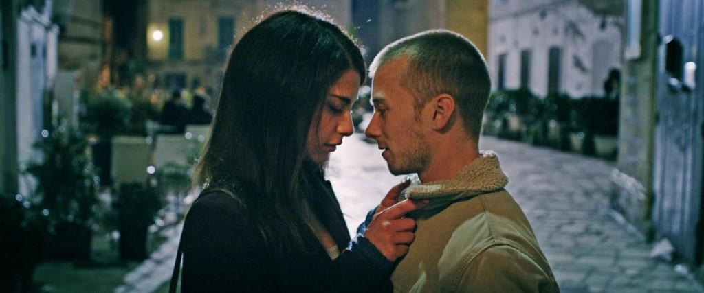 Szene aus Spring: Ein Mann und eine Frau stehen nachts in einer italienischen Stadtkulisse nah voreinander, sie hat ihre Hand an den Kragen seiner Jacke gelegt und senkt den Blick..