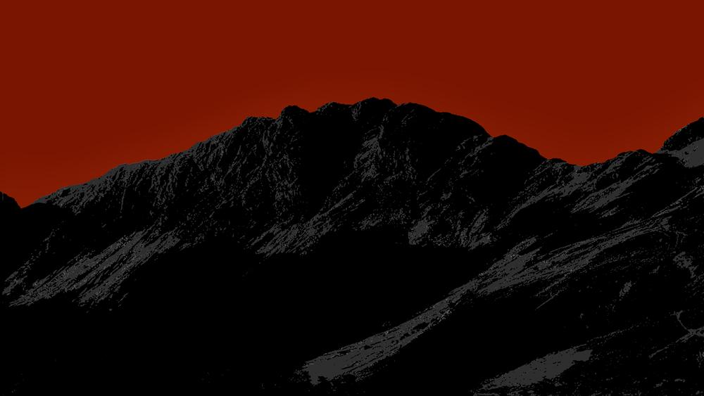 Eine schwarze Berglandschaft vor blutrotem Himmel