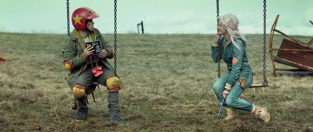 Zwei Schaukeln auf vertrocknetem Gras, auf einer sitzt ein Junge mit rotem Helm, auf der anderen ein blasses Mädchen mit blauem Overall.