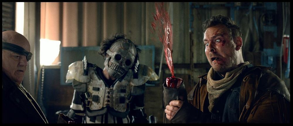 Ein Mann schaut entsetzt auf seinen Armstumpf, aus dem eine Blutfontäne schießt. Neben ihm stehen ein Mann mit einer Augenklappe und einer mit einer Schädelmaske.