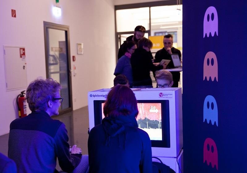 Ein Mann und eine Frau sitzen vor einem Computerbildschirm, sie sind nur von hinten zu sehen. Rechts daneben sind die vier Geister aus Pac Man auf eine Wand gemalt.