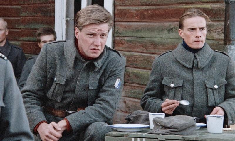 Zwei finnische Soldaten sitzen am Esstisch vor einer Holzwand.