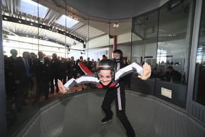 Eine Frau mit Helm schwebt in der Luft beim Indoor Skydiving Bottrop.
