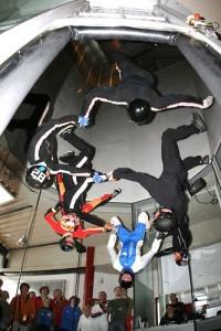 Sieben Menschen hängen im Windtunnel kopfunter von der Decke.