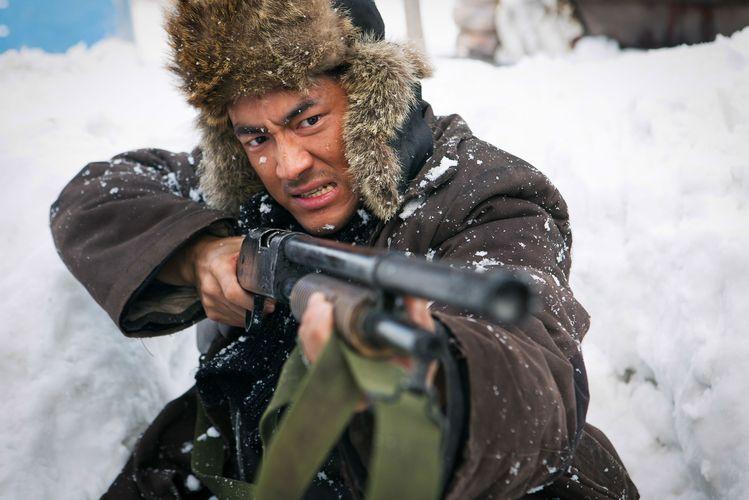 Szenenfoto aus Die letzte Schlacht am Tigerberg: Ein Mann mit Pelzmütze und Gewehr im Schnee.