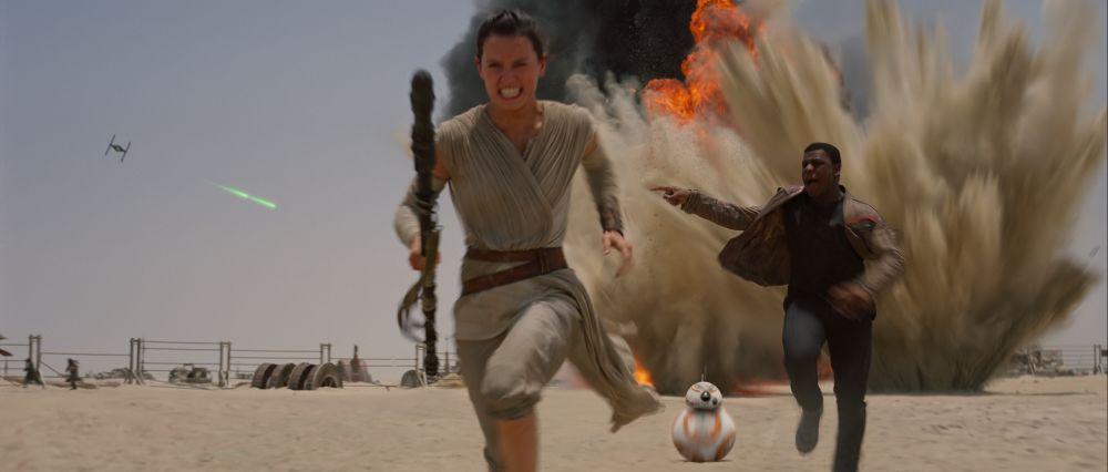 Szene aus Star Wars: Das Erwachen der Macht: Eine Frau, ein Mann und ein kleiner kugelförmiger Roboter fliehen vor einer Explosion im Wüstensand.