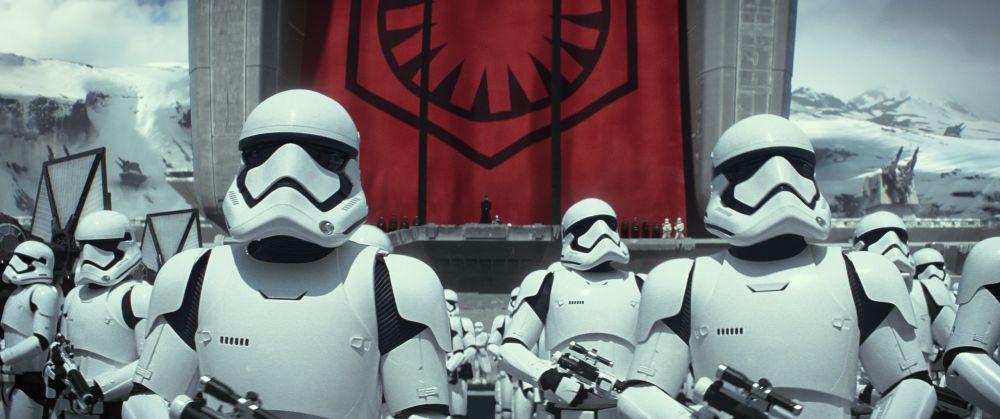 Szene aus Star Wars: Das Erwachen der Macht. Bewaffnete Stormtrooper in weißen Rüstungen mit Helmem stehen vor dem roten Banner des First Order