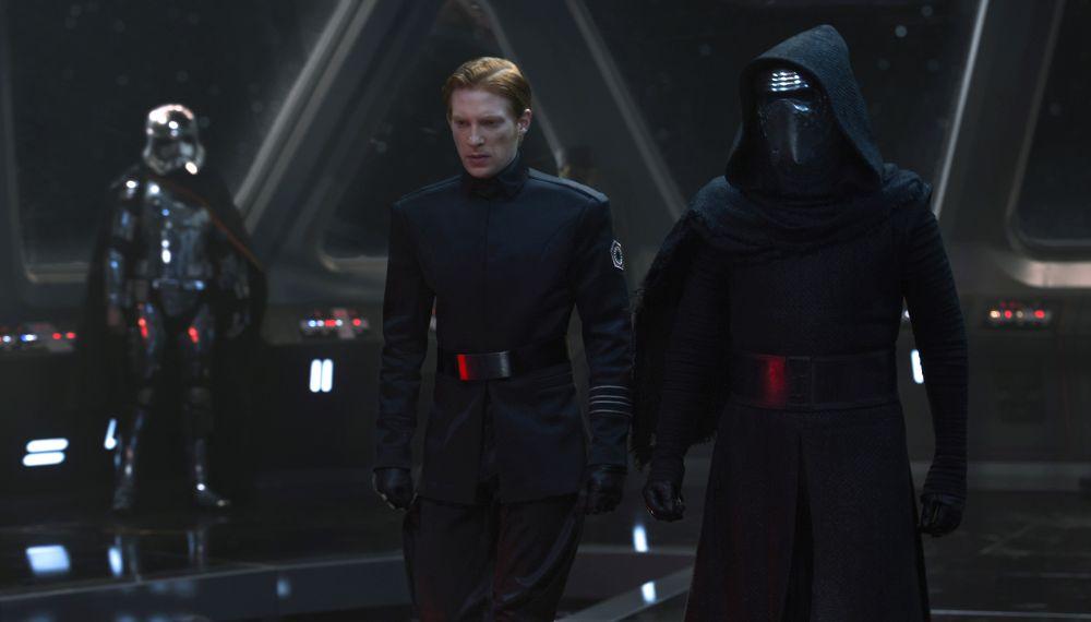 Szene aus Star Wars: Das Erwachen der Macht: Ein Mann in schwarzer Uniform flankiert von zwei Personen in Panzerung mit Gesichtshelmen.